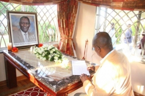 Kiambu Governor William Kabogo signs the condolence book at the Kamulu home of slain Kabete MP George Muchai Sunday. Detectives have been sent to Kampala, Uganda to trace the owner of the car used by the gunman. The car had Ugandan plates. [Photo: Courtesy]